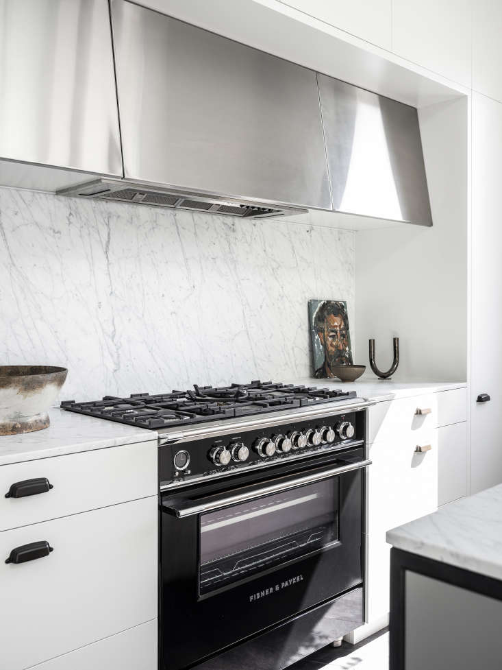 """The 36"""" Classic Dual Fuel Range in black makes a statement in the otherwise all-white Australian kitchen (and offers a large-capacity oven, non-tipping extending oven shelves, precise temperature and burner controls, and a self-cleaning feature, too). Photograph by Tom Ferguson."""