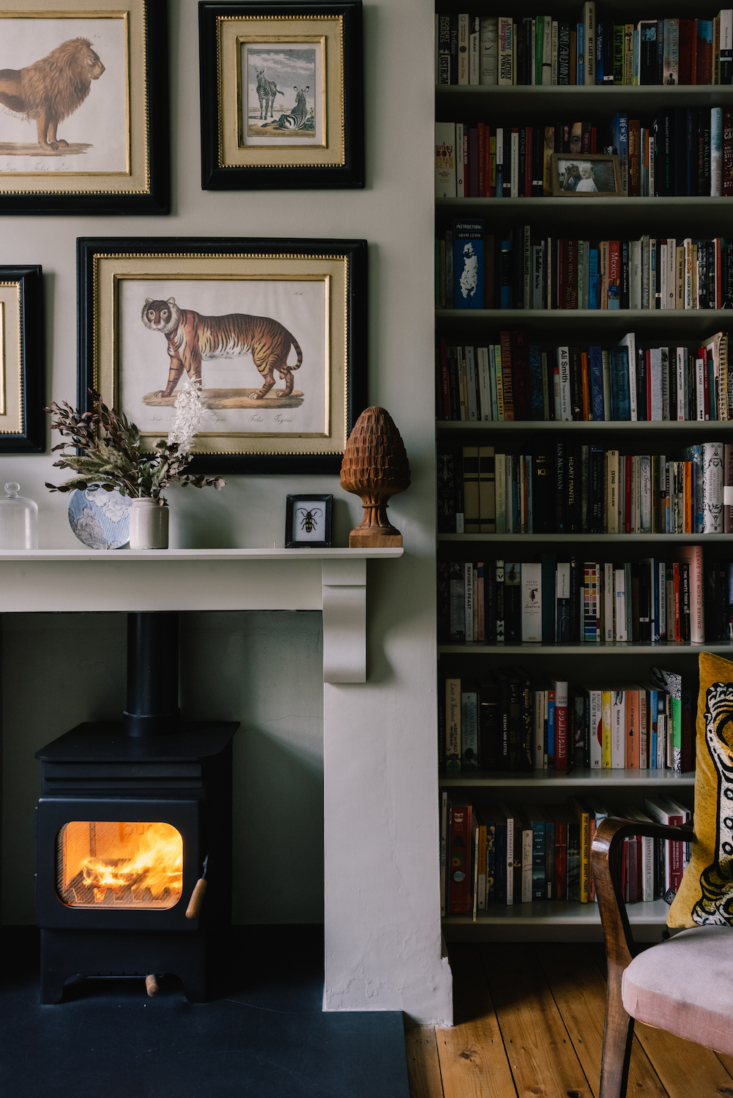 Hanging above the wood-burning stove is a gallery of animal illustrations.