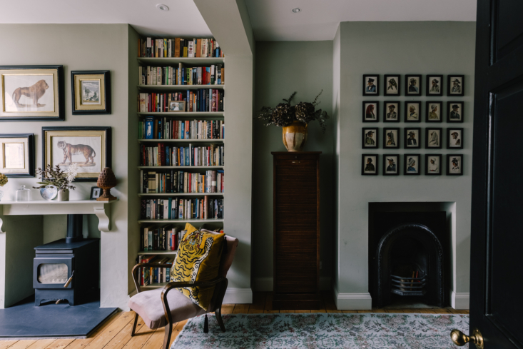 Another sitting area is adjacent to the living room and features a second fireplace. The open room is painted Wattle by Paint & Paper Library.