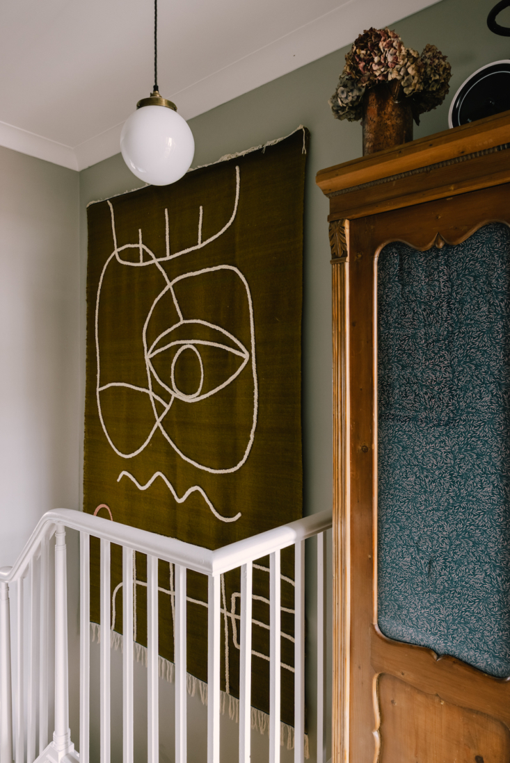 A flat-weave rug featuring an abstract design becomes wall art on the second-floor landing.