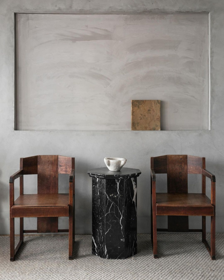 A pair of geometric, mid-century chairs flanks a hexagonal marble table.
