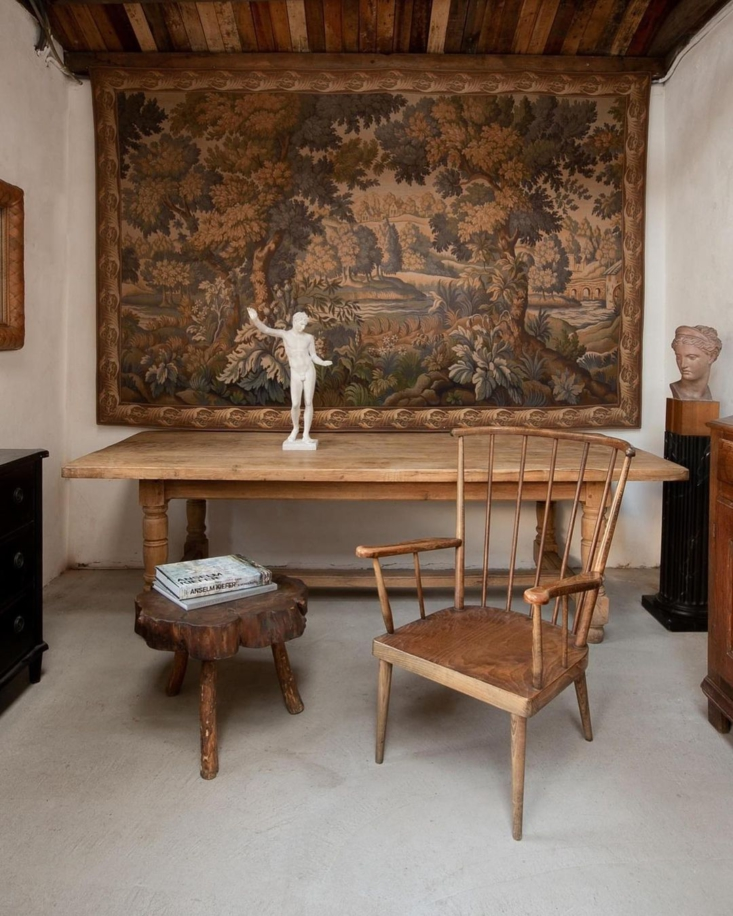 An antique British tapestry mixes well with vintage wooden pieces.