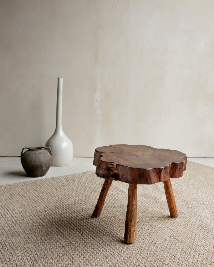 A vintage, handcrafted wooden side table; the original wood-grain is preserved through its organic construction.