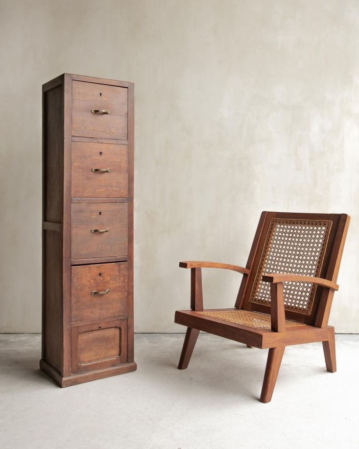 A French wicker armchair, paired with a rustic cabinet piece.