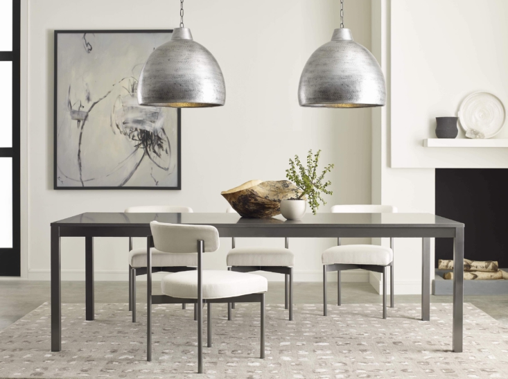 The dining area has become more multi-functional than ever this year. Enter the Essential Parsons Dining Table, available in three sizes, four metal base finishes, and three quartz tops to suit your style and needs. (It makes an excellent workspace or homework zone, too.) The table is paired here with Remy dining chairs, available in the same four metal finishes and hundreds of fabrics and leather. Overhead are new hammered-iron Corinna Pendants in the steel finish.