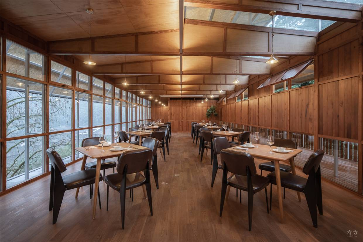 The architects designed a new wood-clad dining area directly atop an existing sandstone wing. Note the ceiling-height windows that let in light and air.