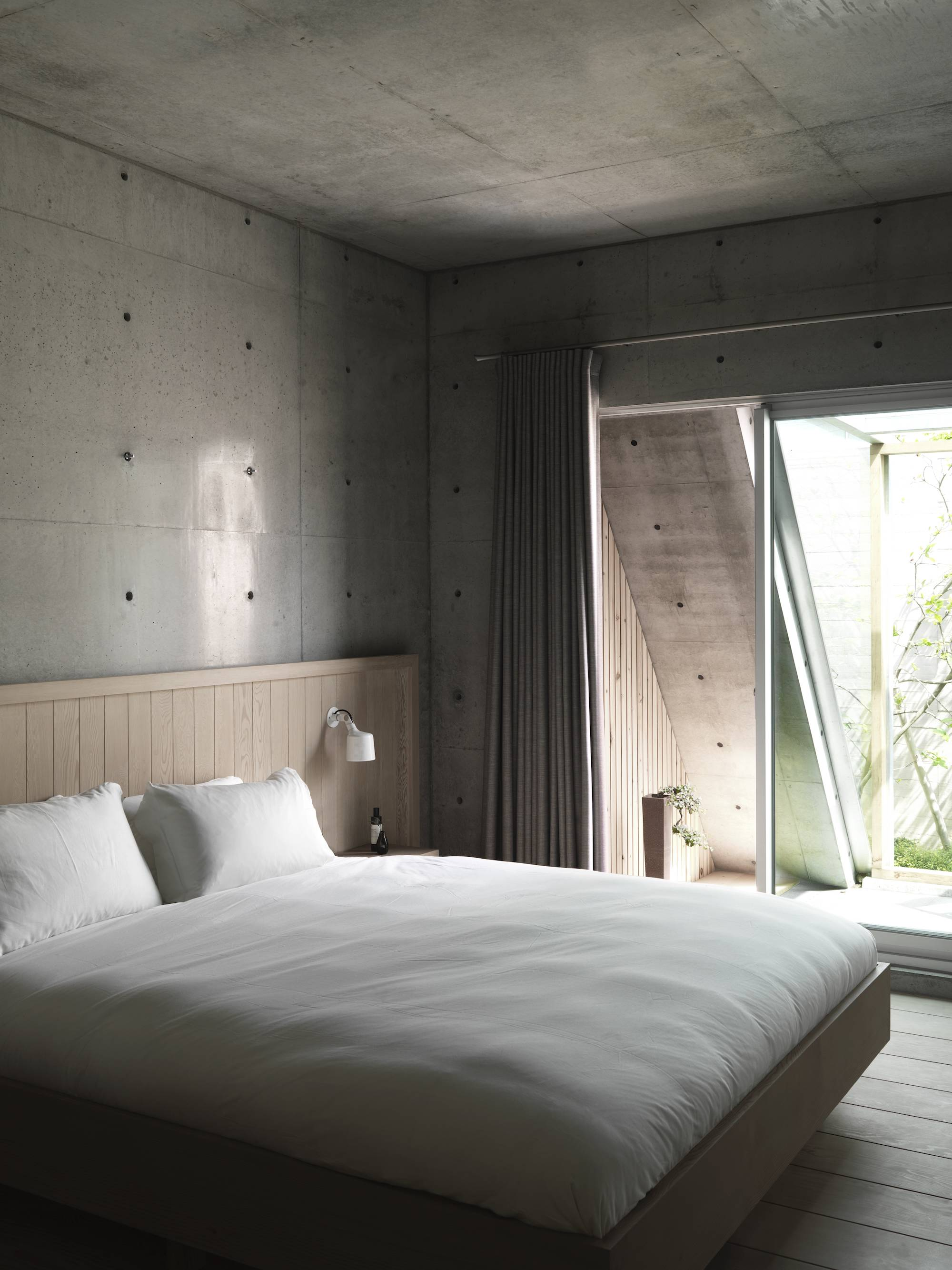 As in the rest of the house, the raw concrete contrasts with the natural wood in the bedroom and bathroom. The bespoke wooden bed was designed by Chiang with an integrated wall spot from Vipp.