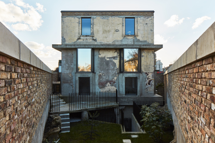 The front elevation and sunken garden where there are three visible types of concrete: Mole Man's handmade batch, which is full of pipes, rubble, and waste; Hackney Council's aerated addition and Adjaye's deliberate sharp edges.