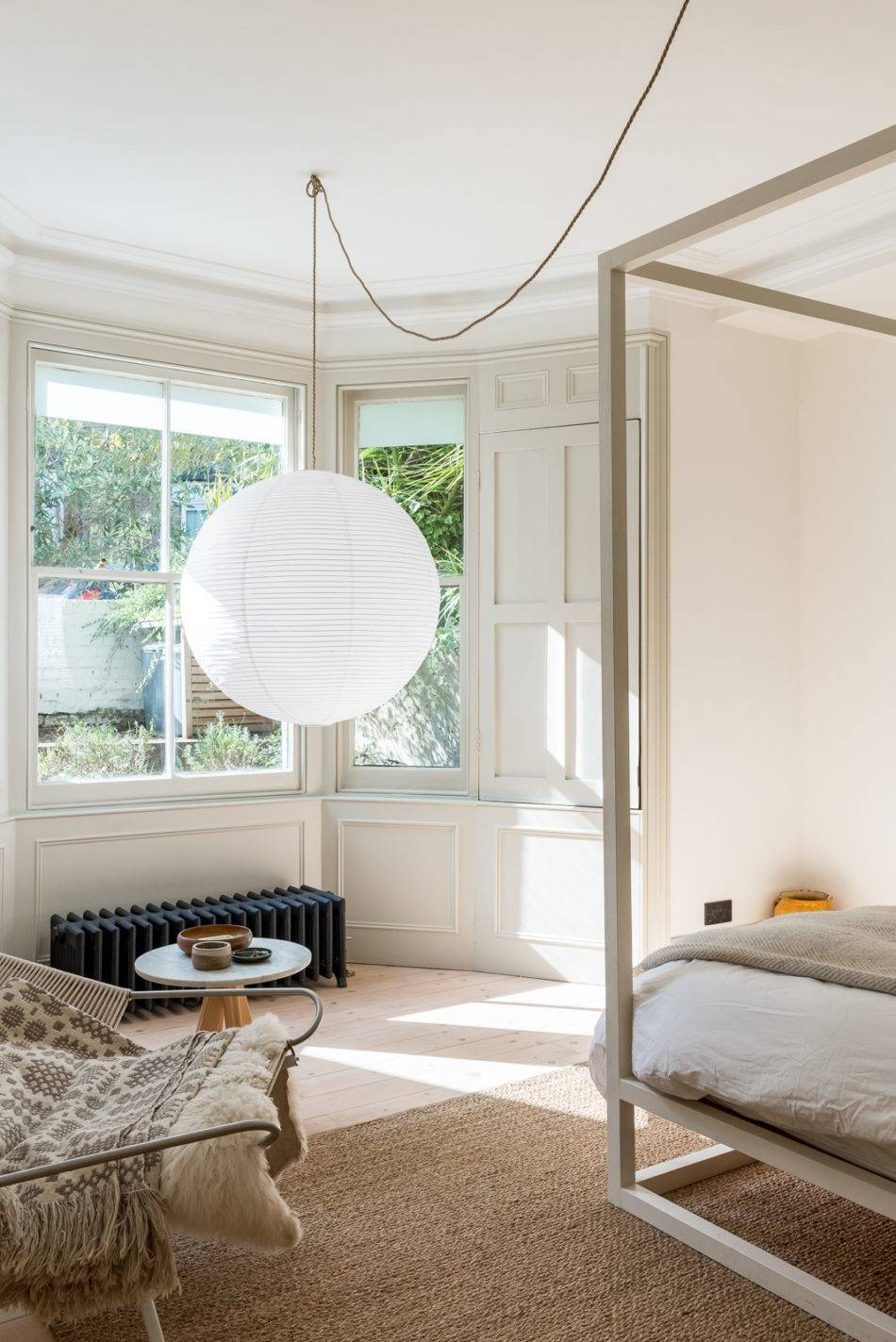 An oversized paper lantern hangs near the window to delineate the sleeping space from the seating area. Photograph from English Translation: A Compact Victorian Gets an Eclectic but Cohesive Makeover.