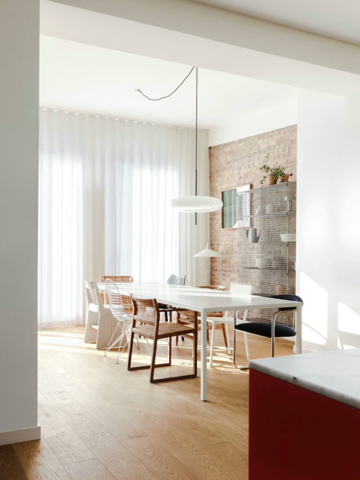 The dining area is open to the kitchen. A motley array of dining chairs surround the table, above which hangs the 65 Suspension Lamp by Astep.