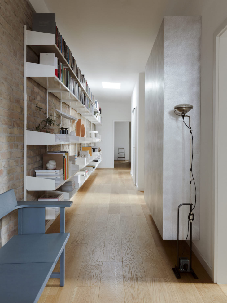 Just off the kitchen is a wide hall with custom wall-mounted shelves.