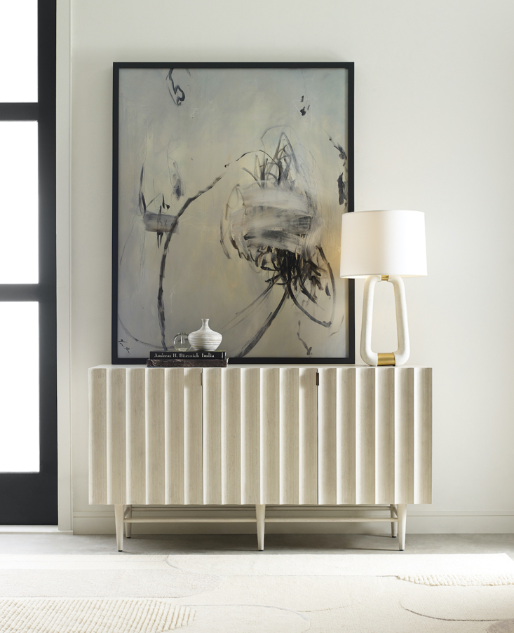 """The new midcentury-inspired Venice Media Console features fluted doors in a soft white hue, ideal for adding a little texture to the dining room, office, or entry. More subtle texture comes from the Art Deco-inspired, tonal-patterned Vivienne Rug by sustainable maker Obeetee. Above is """"Imprint,"""" a limited-edition giclee print on canvas from the company's art collection."""