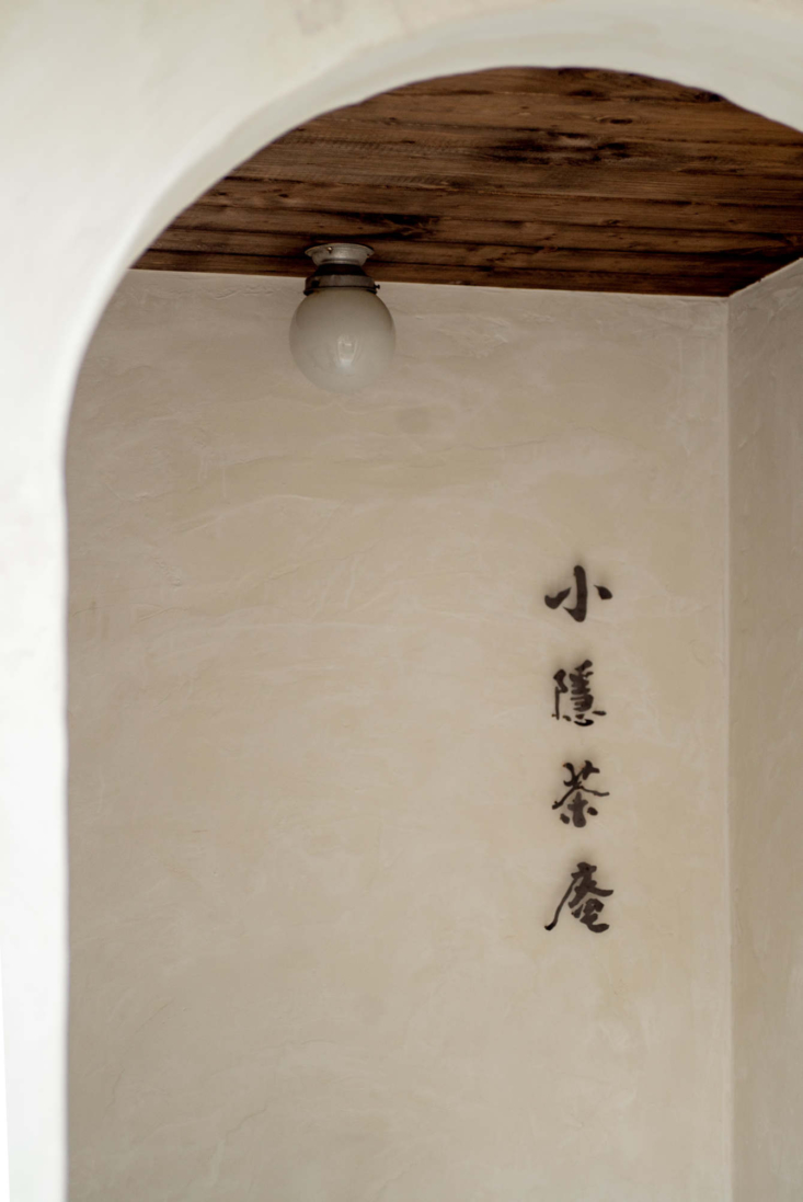 A simple globe light on a wood ceiling in the arched entry—the name Xiao Yin means &#8