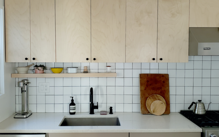 A decent alternative to a terrazzo countertop: MSI Quartz in Iced White. The backsplash is composed of 4- by 4-inch Fireclay tiles in White Wash. The cabinet door knobs are from CB