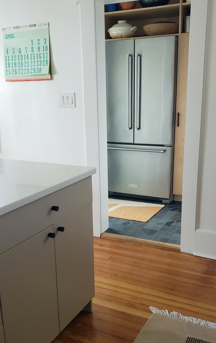 In the pantry, we combined dry storage (with a pullout pantry and open shelving) with cold storage by moving our refrigerator into the back area. We chose MSI Slate subway tiles for the floor.