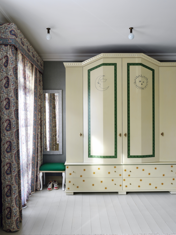 A whimsical painted armoire in a London bedroom.