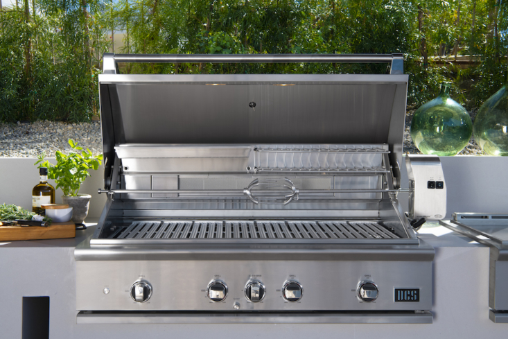 The 48S Grill, Rotisserie and Charcoal is designed to be an all-in-one outdoor cooking appliance, with intuitive built-in lighting to illuminate your cookspace (perfect for after dark); an easy-lift hood that can be maneuvered with one hand; an extra cooking area above the main grill space that can accommodate a broiling pan for slow-roasting, making sauces, or keeping dishes warm; a built-in charcoal smoker tray; and an infrared rotisserie burner. (The rotisserie rod is cleverly stored under the drip pan handle.)