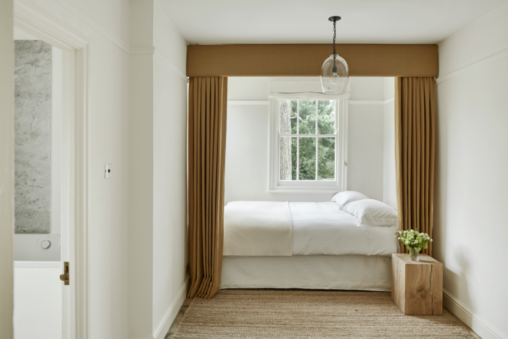 Ochre curtains frame the bed in this petite bedroom. The Clear Lantern light is by Rose Uniacke.