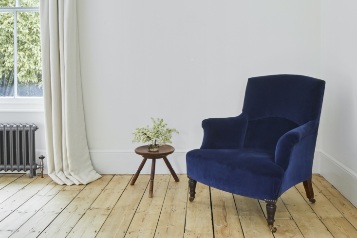 A rare spot of color in the form of an armchair from Colefax and Fowler, reupholstered in navy velvet.