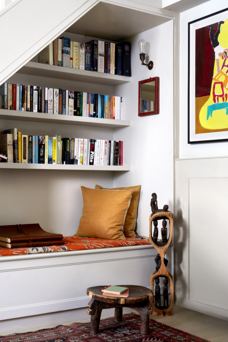 The nook under the stair has a window seat with storage. The African carvings are from Lonika&#8