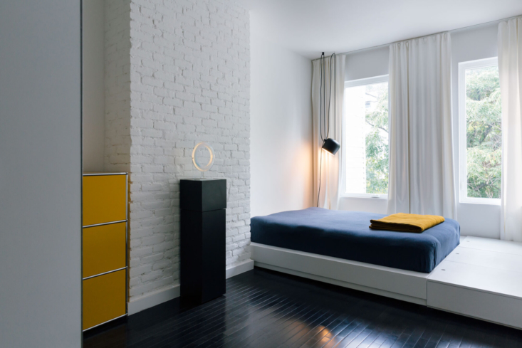 Dashes of yellow in a bedroom. A built-in sleeping platform beneath the windows keeps the space bright and open.