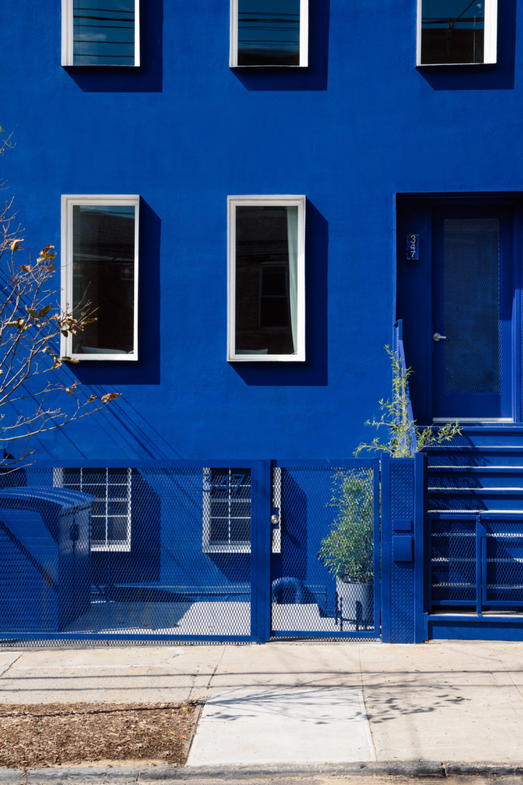 The townhouse is blue all over—fence, waste receptacles, and steps included. The hue is called &#8
