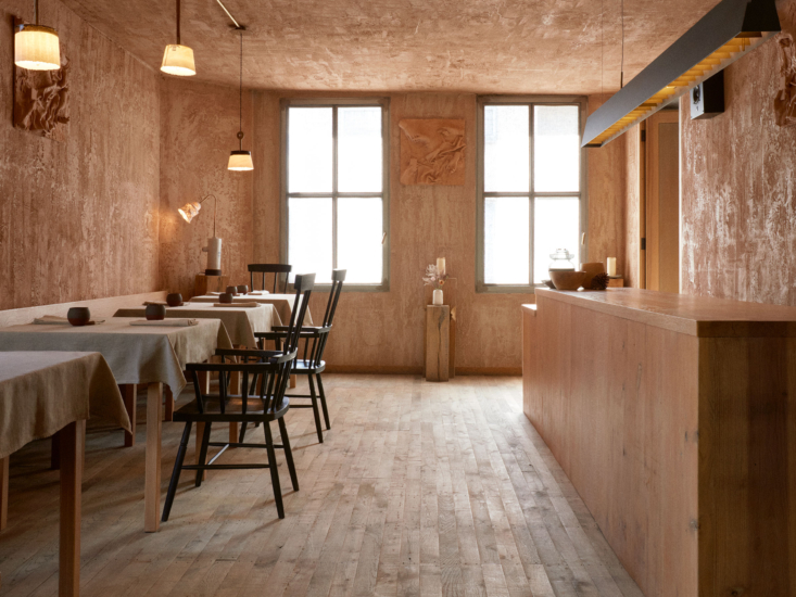 """The restaurant was designed by the Browns in collaboration with 6a architects who orchestrated the conversion of the whole building. The main dining room has raw gypsum plaster walls """"spread roughly by hand, rather than smoothly floated,"""" specifies lead architect Owen Watson. """"Unlike the white plaster in the States or mainland Europe, British plaster is naturally pink."""" (See another London project featuring pink plaster here.)"""