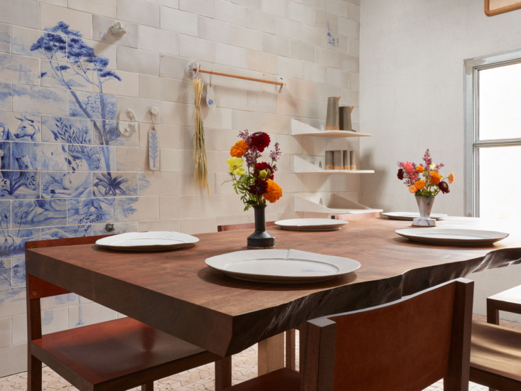 The live-edge Walnut Slab Dining Table and leather-finished Square Guest Chairs are also Tyler Hays designs from BDDW, as are the pitchers and glasses on the shelves. See more of his ceramics here and here.