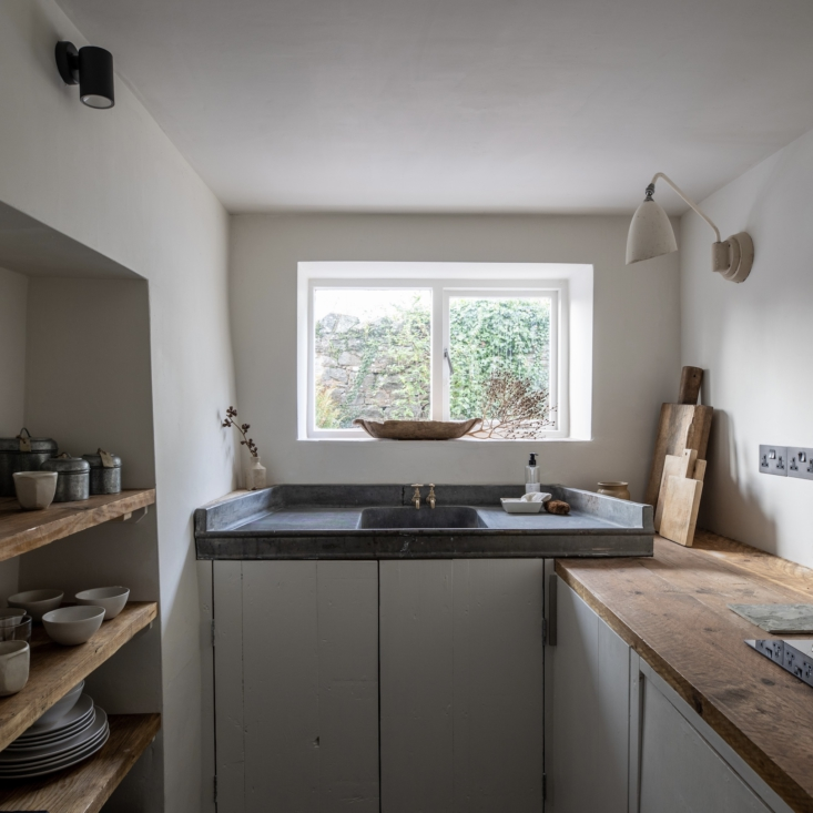 The small but perfectly configured kitchen has been fitted with worktops made from reclaimed scaffold boards, reclaimed wood for the cabinet doors, and a salvaged zinc sink with brass garden taps. The kitchen shelves are stacked with tactile, hand-thrown ceramics created for Harp Studio by ceramicist Chloe Charrington.
