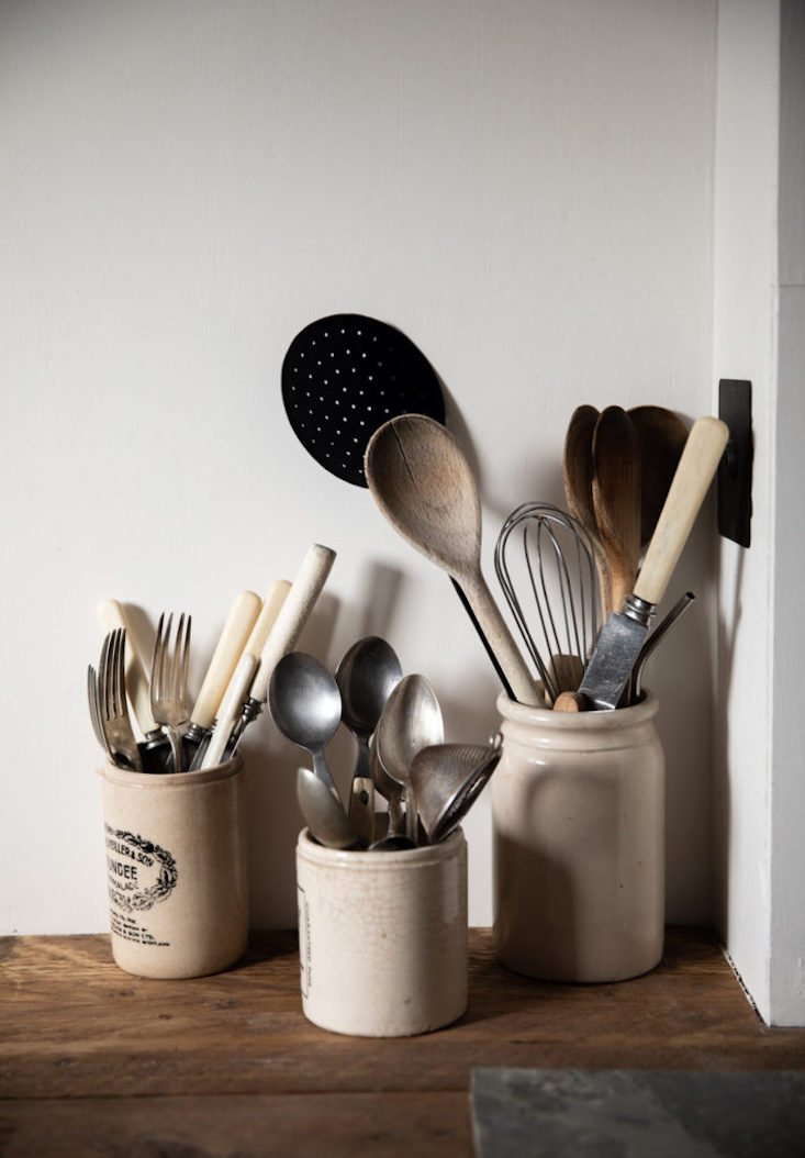 A mix of vintage flatware and cooking utensils are displayed in vintage marmalade jars.