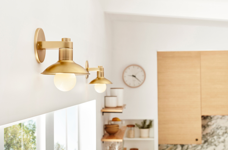 Then, add support lighting to brighten the spaces around your overhead lighting and illuminate specific workspaces or details you want to highlight, like open shelving. Here, a pair of Crawford Single Wall Sconces ($