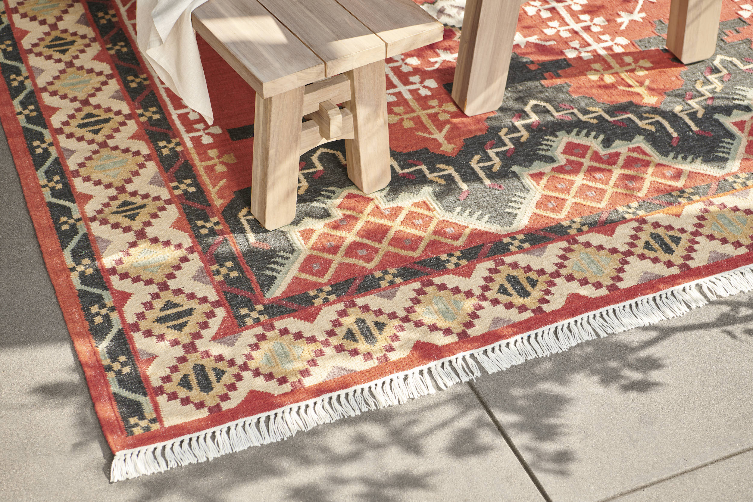 """Just as you would indoors, define your outdoor living """"room"""" with a rug—a sustainably crafted and easy-to-clean indoor-outdoor one, made from recycled polyester (PET) for long-lasting use. This one is the Ortakoy Indoor/Outdoor Rust Flatweave Rug ($449 for the 5' by 8' size), made from 0 percent recycled-polyester yarn."""