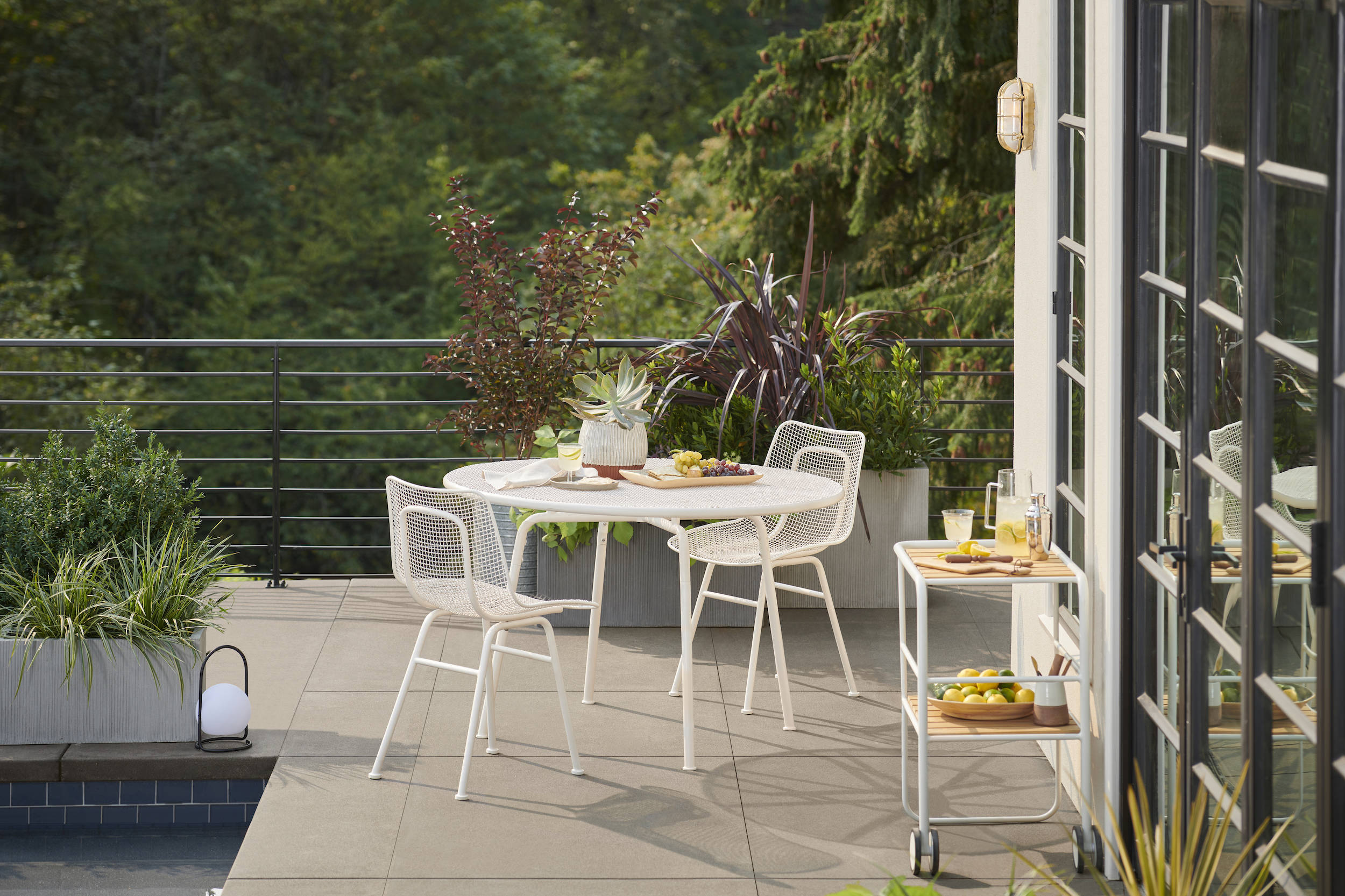 Take dinner (and breakfast, lunch, and happy hour) outdoors. Create a fresh-air dining space you'll use all season long with the midcentury-inspired Prineville Outdoor Dining Collection, including the Prineville Table ($699) and Prineville Arm Chairs ($399 each) shown here in white, crafted with sturdy wrought-iron mesh and powder finished for year-round durability.