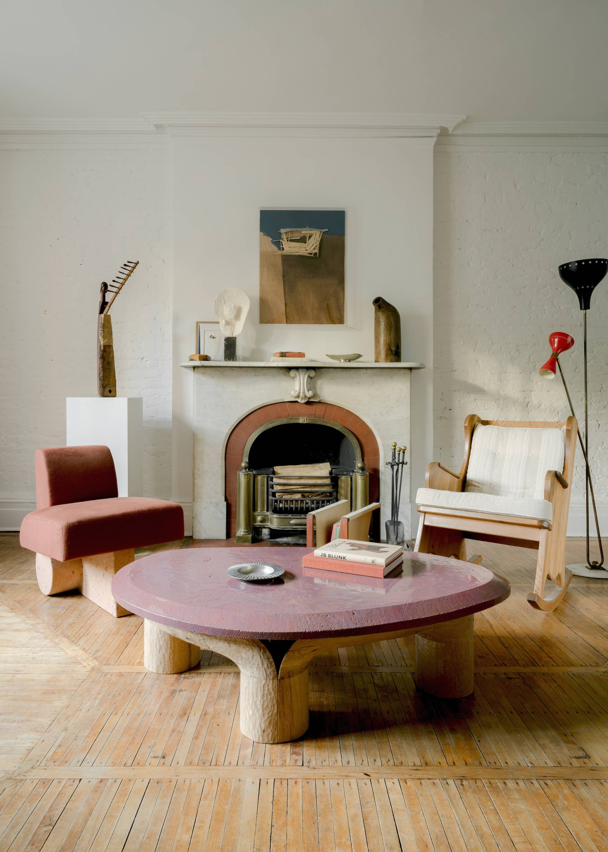 Ian Felton's glazed lava stone Sacha Coffee Table, perched on a hand-carved wooden base, is flanked by his glazed lava stone Kosa Side Chair and a 30s Lovö rocking chair by Swedish designer Axel Einar Hjorth. The artwork above the fireplace is by Japanese artist Tadashi Kawamata and the plaster lamp on the mantle is by Minjae Kim, a Korean artist working in NYC.
