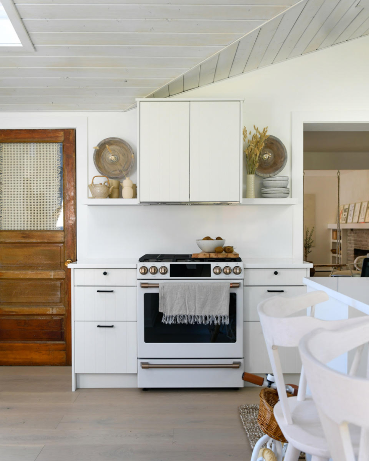 Handmade sconces by Bass & Bennett flank the GE Cafe Appliances stove, in matte white. The vintage door leads to the old kitchen, now a study.
