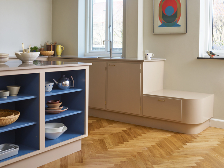 At the end of the kitchen counter, a step with a rounded corner a serves as a storage bench and place for kids to stand on and &#8