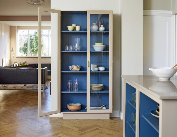 A two-toned cabinet with glass doors holds the family dinnerware. The oak herringbone floor extends into the adjacent living room.