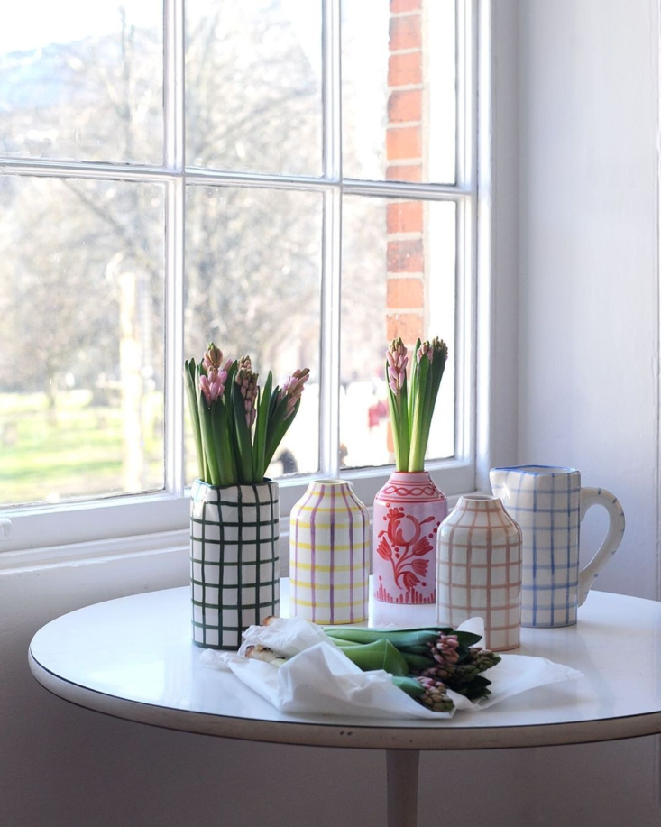 A collection of Vaisselle pitchers and vases—including, from left to right, the Drink Me Jug in Forest Green and White Gingham, Genie In a Bottle Vase in Lilac and Red Floral, Genie In A Bottle Vase in Nude Gingham, and Drink Me Jug in Baby Blue and White Gingham, each £75—via The Hambledon.