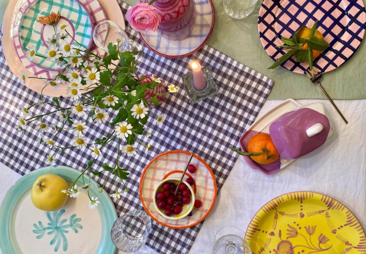 A colorful, maximalist tablescape. The blue-painted plate is the Bon Appetit Plate in Mint, made to order (£65).