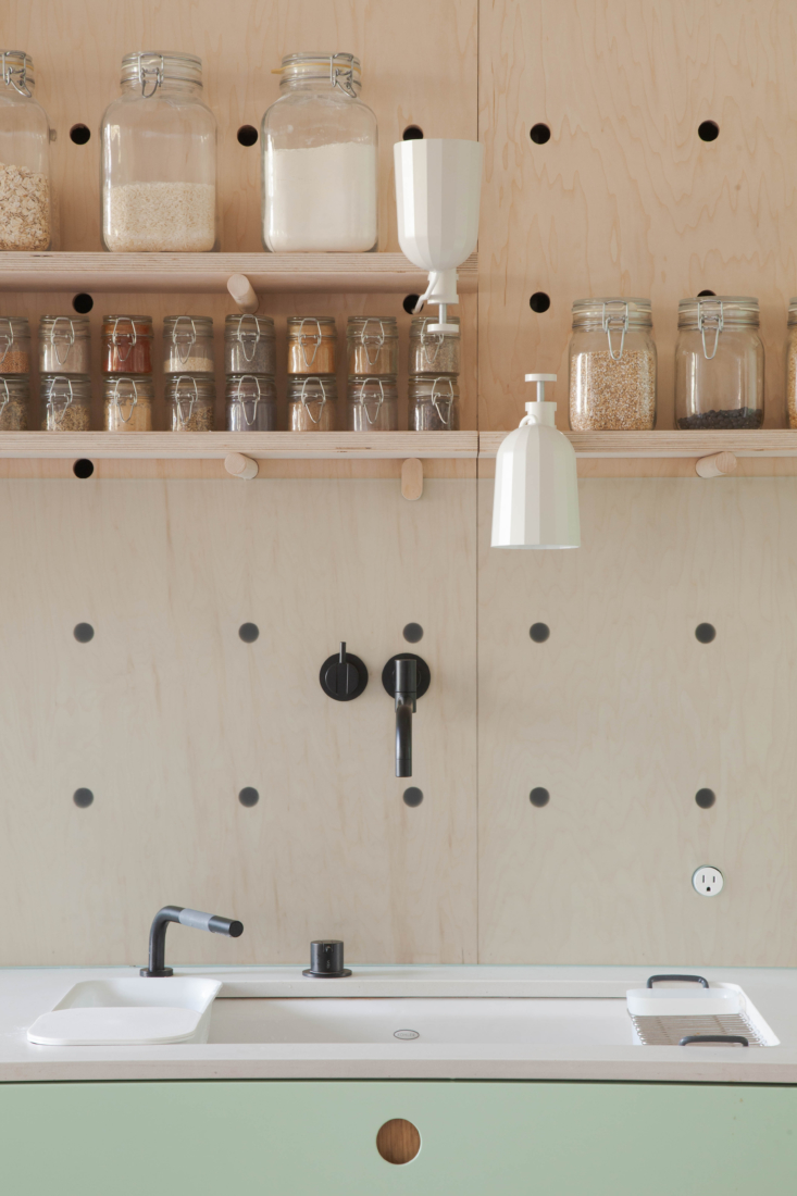 A slim and unobtrusive single outlet in a charming pegboard behind a kitchen sink. The