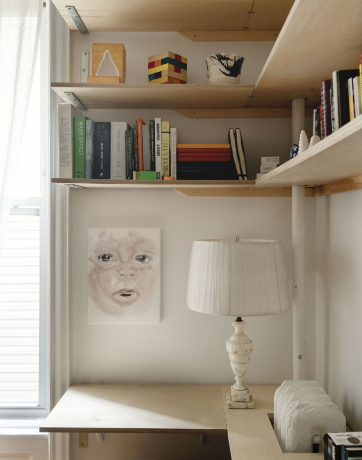 A cutout plywood desk wraps around an old-fashioned cast iron radiator.