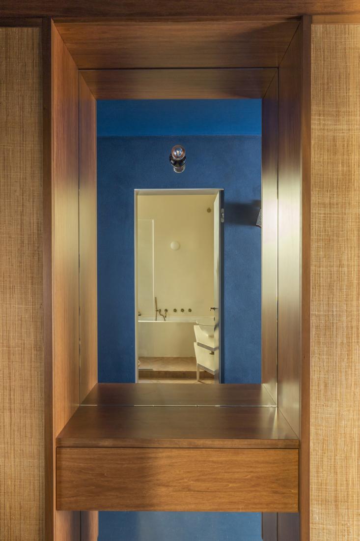 A mirror in a hallway closet area reflects the main bathroom.