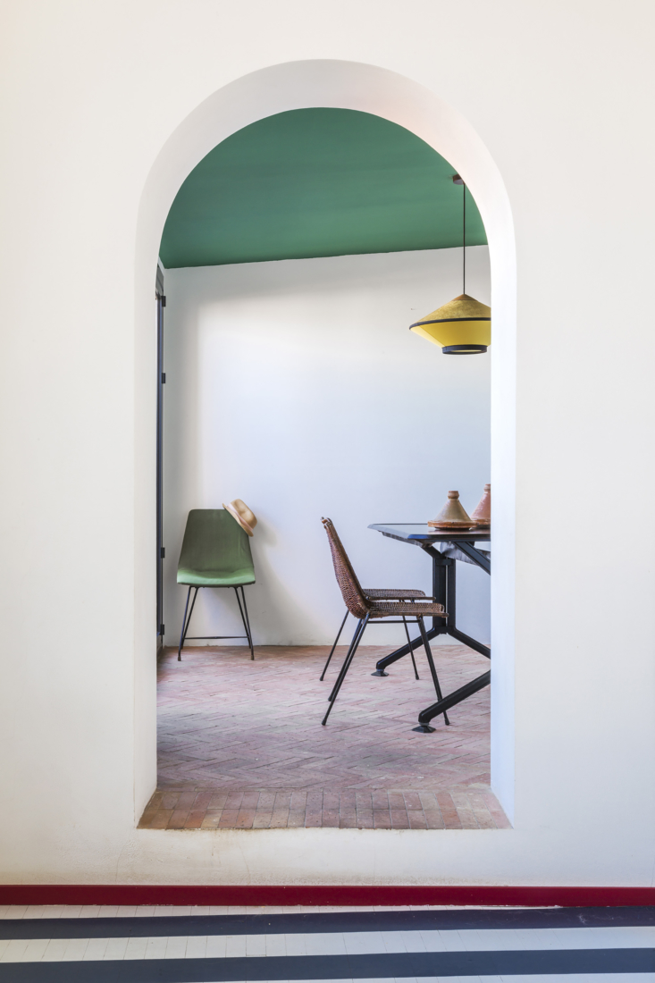Through an archway to the dining area, laid with terra cotta flooring.