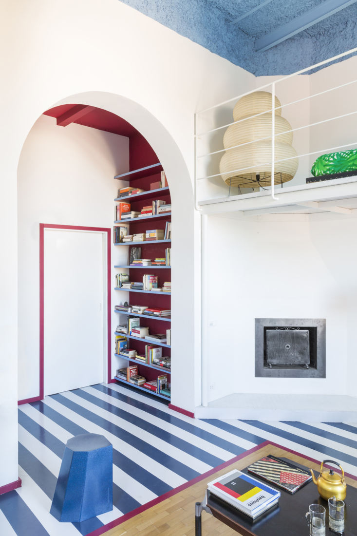 The homeowners—a couple with two children—tasked Tattolo and Freschetti with creating a playful, bright space reminiscent of vacation. Mission accomplished, with white archways and parquet floors painted over in bold blue and grey. Note the stripe of red paint continued from the built-in bookshelf around the front door, baseboards, and an exposed, unpainted patch of parquet.