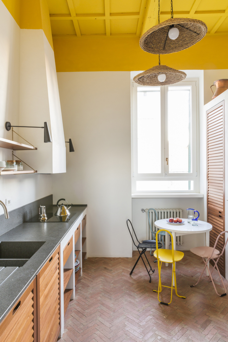 The herringbone-patterned tile continues into the kitchen, where the architects painted the original wooden ceiling a cheerful yellow.