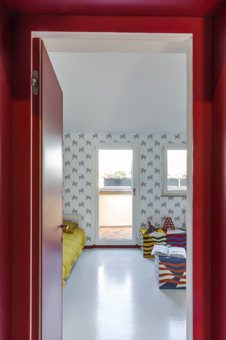 An all-red hallway is a reference to the red stripe by the entry and connects the bright, open common areas and the more saturated sleeping spaces. Shown here is the kids&#8