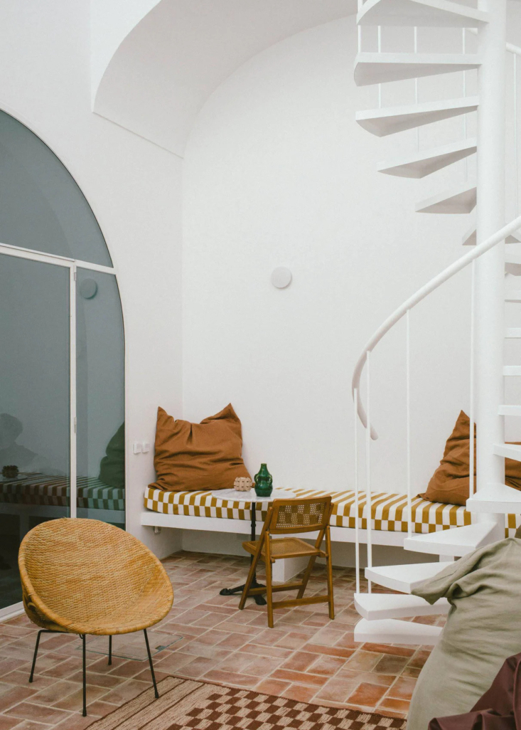 One Two Three Minimalist Guesthouses on the Coast of Portugal Pools Included A built in lounge area is fitted with a summery striped cushion.