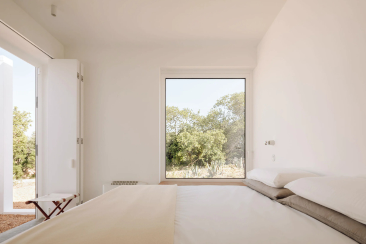 One Two Three Minimalist Guesthouses on the Coast of Portugal Pools Included One of the newly added bedrooms on the lower level features fold out doors and oversized windows looking out at orange trees.