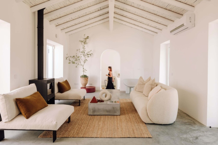 The former farmhouse turned living area, with concrete floors, simple woven mats, and white-washed ceilings.