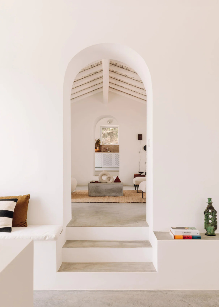 A series of archways and steps lead into the living area and kitchen beyond. The sculptural green candleholder at right is an example of traditional Moroccan tamegroute pottery; Julie and I recently became admirers.